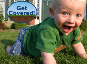 Picture of a baby crawling on a lawn in front of a house. The Get Covered! logo is in the left hand corner.